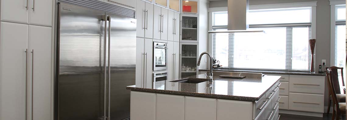 image of kitchen with white cabinets and black countertops